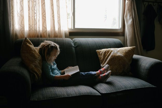 Little girl reading on a couch