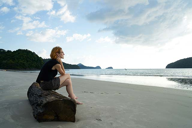 Woman sitting on rock looking over sea thinking about El-Elyon